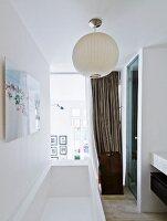Modern bathtub below white spherical lamp in front of glass wall