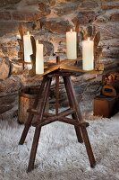 Old wooden reel with four candles used as Advent wreath on flokati rug in front of stone wall