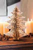 DIY Christmas tree made from cut sheet music, lit candles and wreath of pine cones