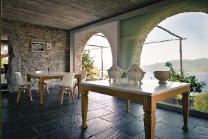 Antique china tureens on table and dining table with modern shell chairs in front of panoramic windows with sea view