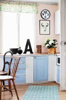 Simple, nostalgic country-house kitchen in pale blue and white with various wooden chairs