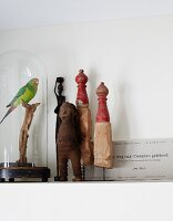 Vintage figurines of humans, miniature wooden sculptures and stuffed parrot under glass cover