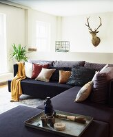 Black corner sofa with many scatter cushions in front of hunting trophy on wall
