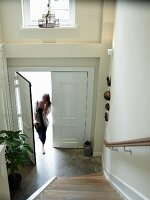 View down staircase of woman in house entrance