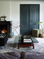 Low coffee table with smoked glass top on vintage-look rug in front of double doors painted dark grey