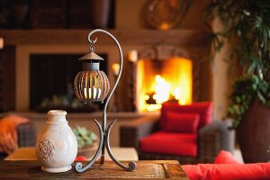 Pot and candle lantern on table against lit fireplace in living room; Scottsdale; USA