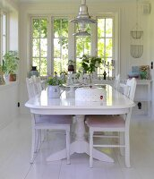 White dining table and chairs in dining room with white wooden floor
