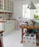 Toy cooker in front of old workbench converted into kitchen counter in Scandinavian kitchen-dining room with white wooden floor