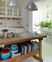 Old workbench converted into kitchen counter in Scandinavian kitchen with open doorway leading to dining room