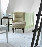 Antique easy chair with ornately patterned upholstery in front of stair rail in attic room with white wooden floor