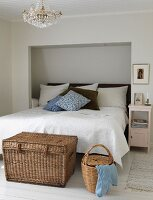 Wicker trunk at foot of double bed with headboard in niche in white bedroom