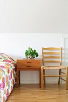 Bedside table, pale wooden chair and bed with bright bedspread in attic room