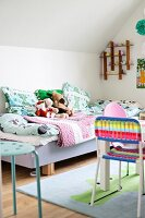 Child's bed with colourful blankets, pillows and soft toys; colourful plastic chair at play table in foreground