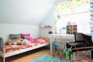 Colourful bed linen and soft toys on metal bed, retro doll's pram and desk below window