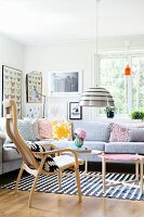 Seating area with retro scatter cushions on corner sofa and Scandinavian wooden furniture; gallery of pictures on wall in background