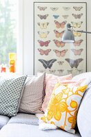 Retro scatter cushions on corner sofa and picture of butterflies in background