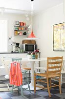 Danish, classic Semi lamp above Tulip table and mixture of chairs in youthful, retro kitchen-dining room