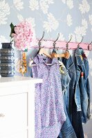 Denim clothing hung from hooks on floral wallpaper; hydrangea bloom in retro vase on white chest of drawers