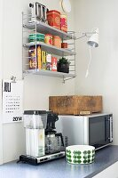 Microwave, coffee machine and bowl on kitchen worksurface; vintage toaster and clip-on lamp on wall-mounted shelves in corner of retro kitchen