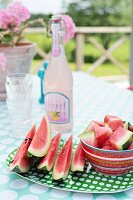 Green and white spotted plate, red striped bowls and sliced watermelon in front of retro lemonade bottle on table in summery garden