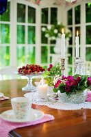 Table set with bowl of flowers, candles and fresh strawberries