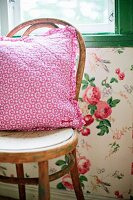 Pink floral cushion on Thonet chair against wall with floral wallpaper