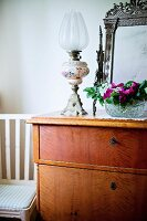 Paraffin lamp and bowl of flowers on simple wooden chest of drawers