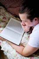 Teenager reading on bed