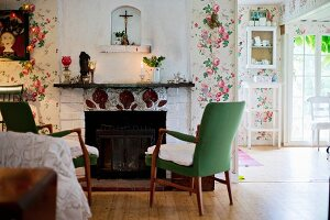 50s armchairs with green upholstery in front of open fireplace in rustic interior