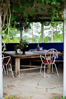 Rustic wooden table and white, delicate metal chairs on stone loggia floor