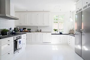Spacious, Scandinavian-style white kitchen with white worksurfaces and stainless steel appliances
