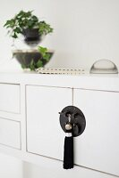 Oriental tassel hanging from black, Oriental-style cabinet handle fitting