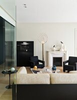 View over sofa of elegant, dark armchairs and brass standard lamp in minimalist living room