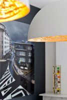 Detail of two pendant lamps with white and gold lampshades; photographic art on black wall in background
