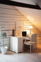 Vintage-style home office below wood-clad sloping ceiling; gable-end wall made from whitewashed wooden beams