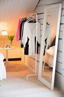 White, feminine attic room with full-length mirror, clothes rack and tulips on bedside table in background