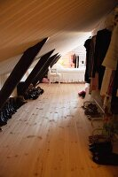 Clothes rack and shoes below wood-clad sloping ceiling