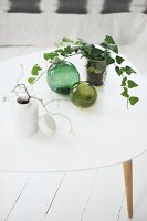 Sprigs of leaves in various vases and decorative, green glass spheres on white coffee table