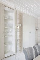 Backrests of upholstered dining chairs and fitted display cabinets in interior with white, wood-clad walls and ceiling