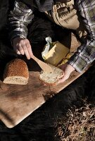 Woman's hands holding bread and butter outdoors with wooden board and fur blanket