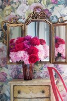 Peonies on vintage chest of drawers below ornate vanity mirror on wall with romantic floral wallpaper