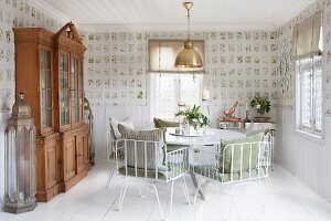 White metal chairs with cushions around round table and glass-fronted dresser in dining room with botanical wallpaper and white wooden floor