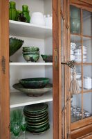 Glass-fronted cabinet with open door and view of green ceramic crockery