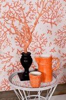 Orange jug and beaker next to orange branch in black vase in front of patterned wallpaper