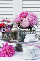 Romantic arrangement of peonies & silver accessories on table