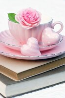 Pink teacup on stack of books decorated with roses & heart ornaments