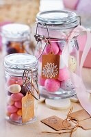Easter eggs in preserving jars decorated with ribbons and paper tags