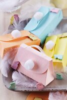 Colourful, spring-themes paper gift boxes shaped like handbags with handles and pompoms