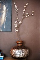 Branch of white flowers in ornate wooden vase and partially visible picture on brown wall