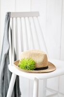 Summer hat with green chrysanthemum 'Anastasia' in hat band on white wooden chair